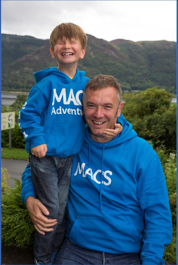 Image shows child with a MACS condition and their parent