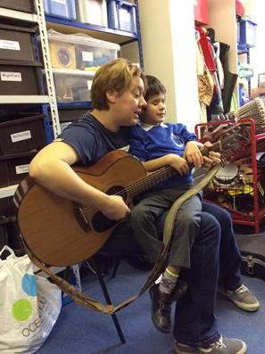 Image shows child with a MACS condition enjoying a music therapy session