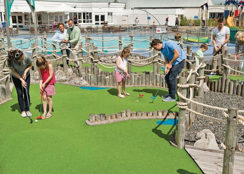 Image shows a family playing mini golf