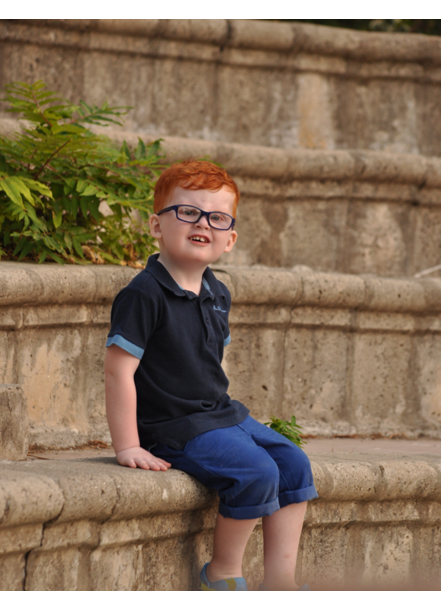 Image shows a child with a MACS condition sitting on stairs